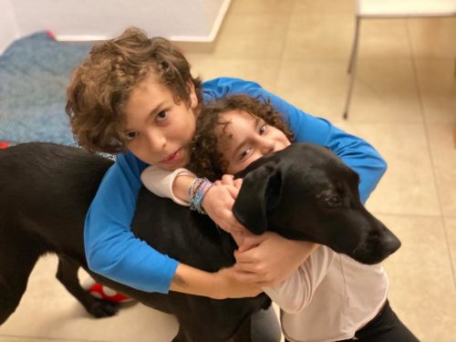 צ׳יקה כלבת לברדור שחורה מעורבת מחובקת עם ילדי משפחת לוין